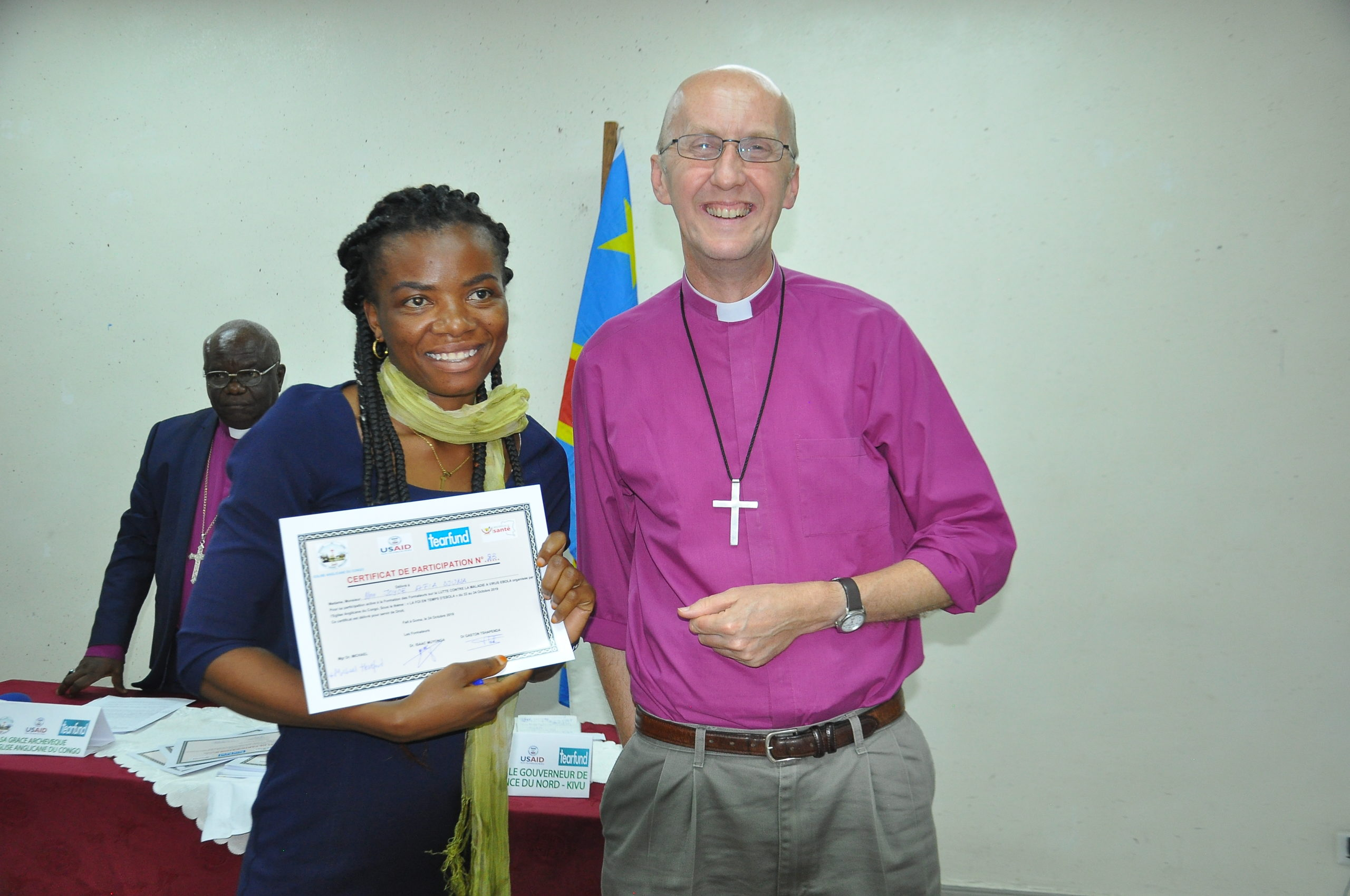 Faith leader (left) receives certificate of completion of Ebola training.