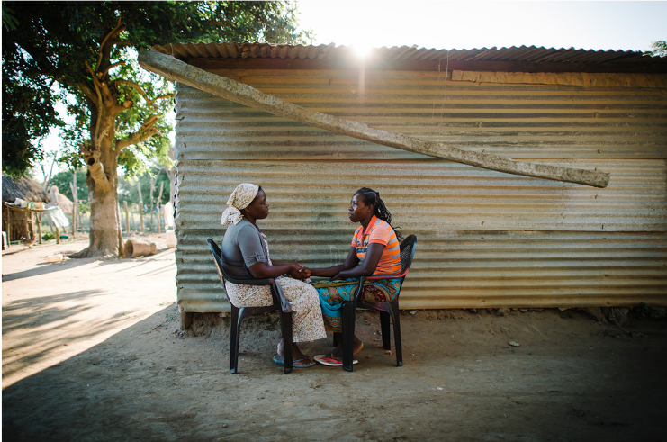 A woman involved in a Care Group program in Mozambique to share health information with her neighbor talks to another woman about TB.