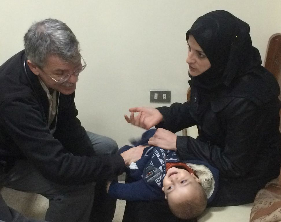 Doctor examines an infant and talks to a mother in Syria.