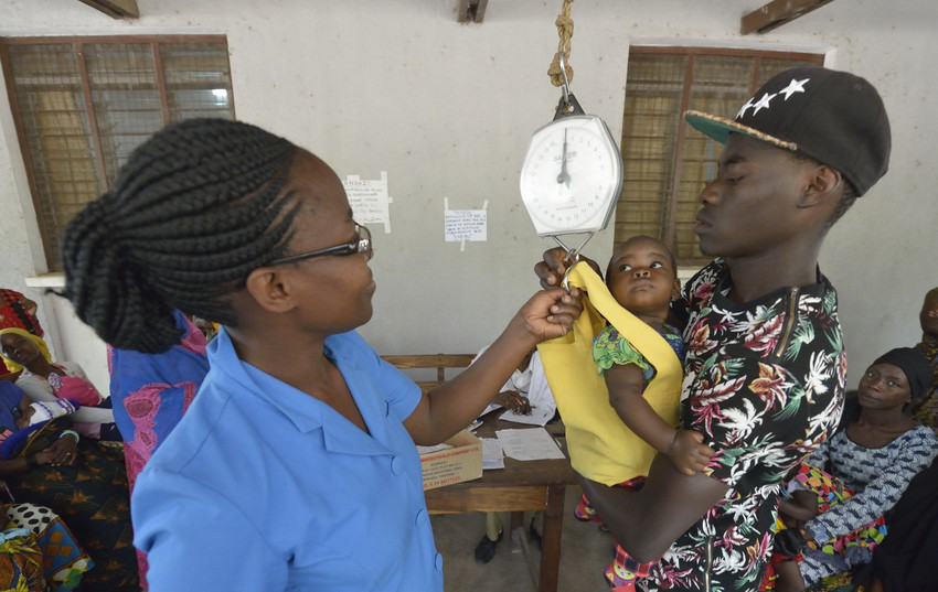 A man holds a baby to be weighed by a health worker in a nutrition program in Tanzania.