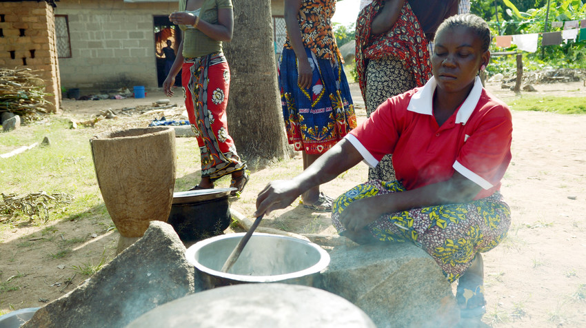 A woman stirs food cooking over a fire as part of a nutrition program in Tanzania
