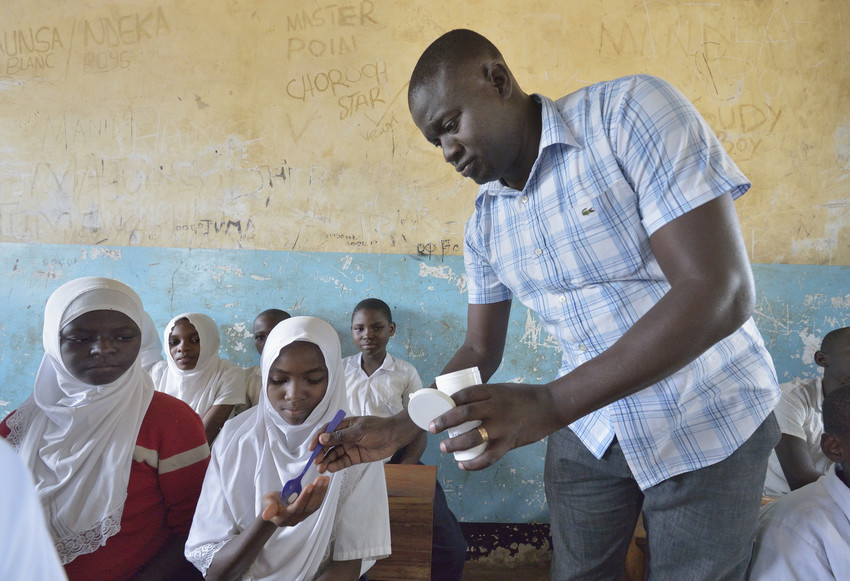 A man distributes medicine to fight neglected tropical diseases to students in Tanzania.