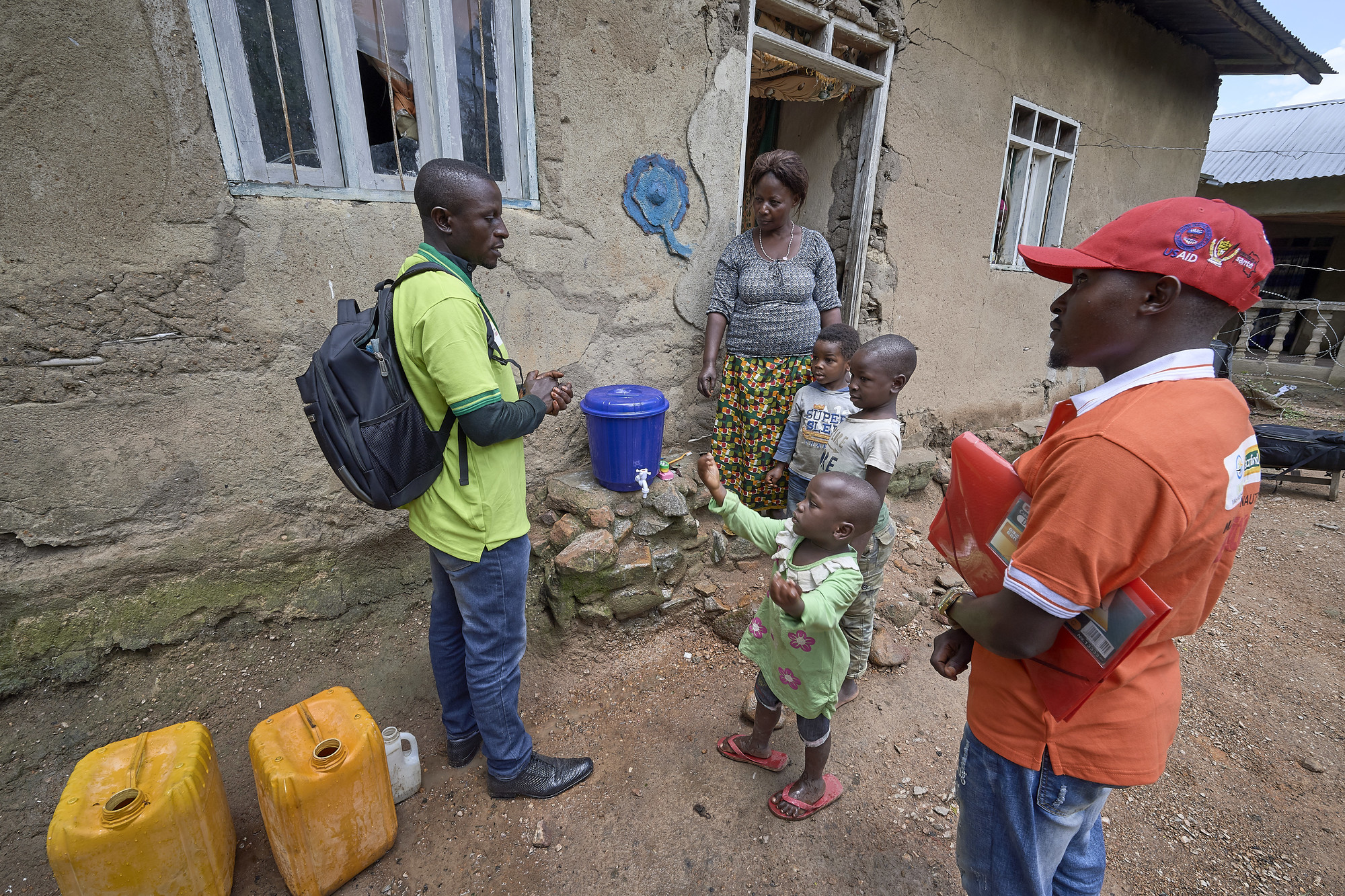 A community health promoter talks with children in front of their home in Beni, a city in eastern Democratic Republic of the Congo that was hard hit by the Ebola outbreak that began in 2018.