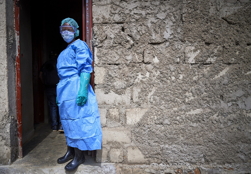 A nurse standing outside a clinic with stone walls wears protective clothing in a clinic in Beni, a city in eastern Democratic Republic of the Congo that was hard hit by the Ebola outbreak that began in 2018.