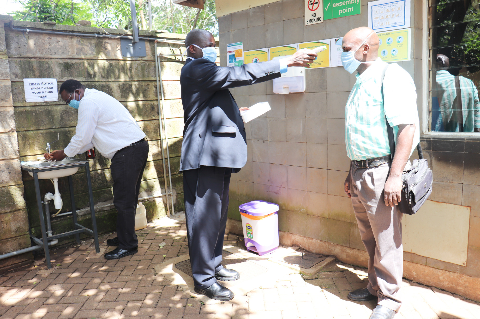 A man takes a temperature reading from a visitor at the Christian Health Association of Kenya gate, located in Nairobi, as a staff member washes his hands after having his temperature taken.