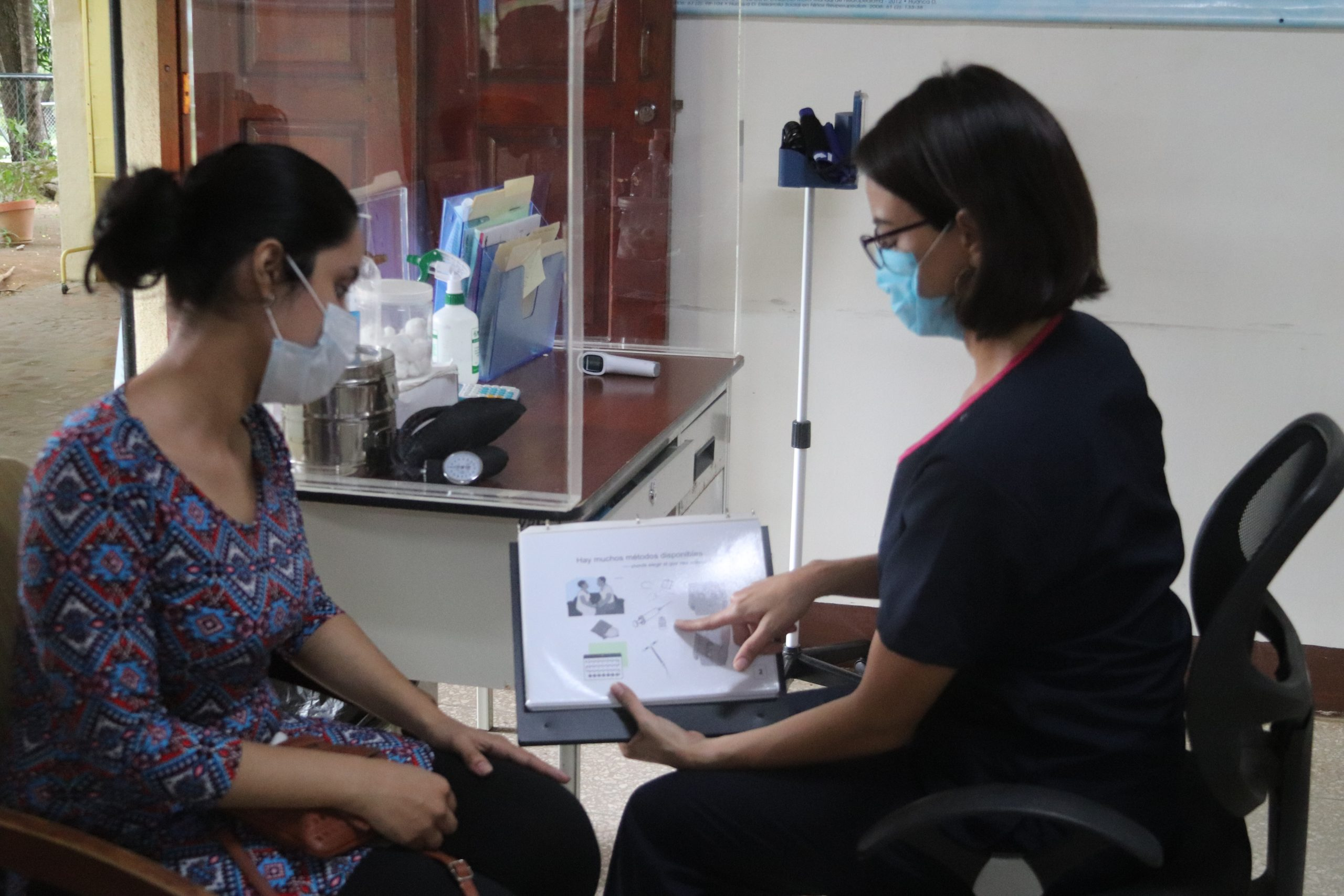 A doctor shows family planning methods in a training book to a patient.