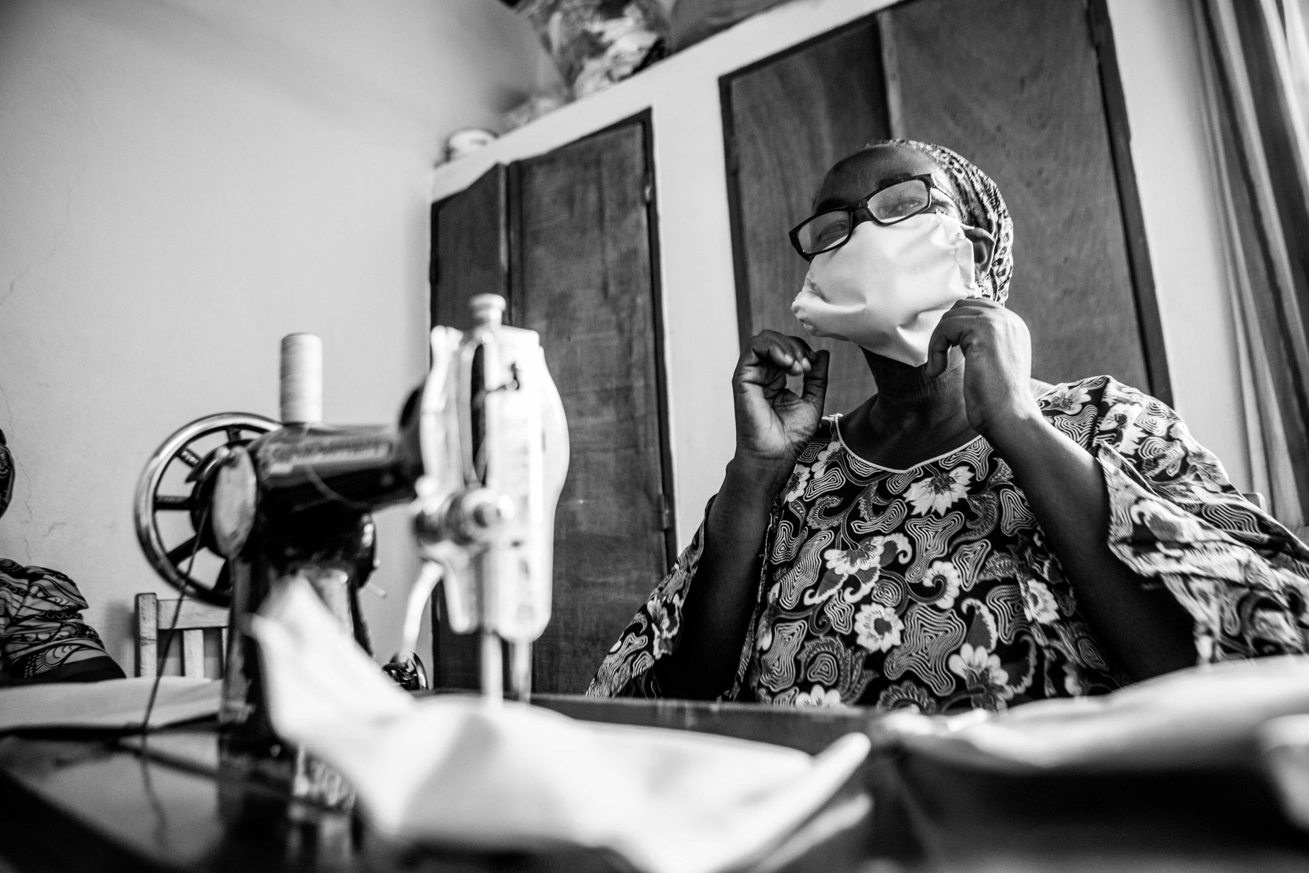 A woman wearing a face mask sits at a sewing machine at the CURE Niger Hospital