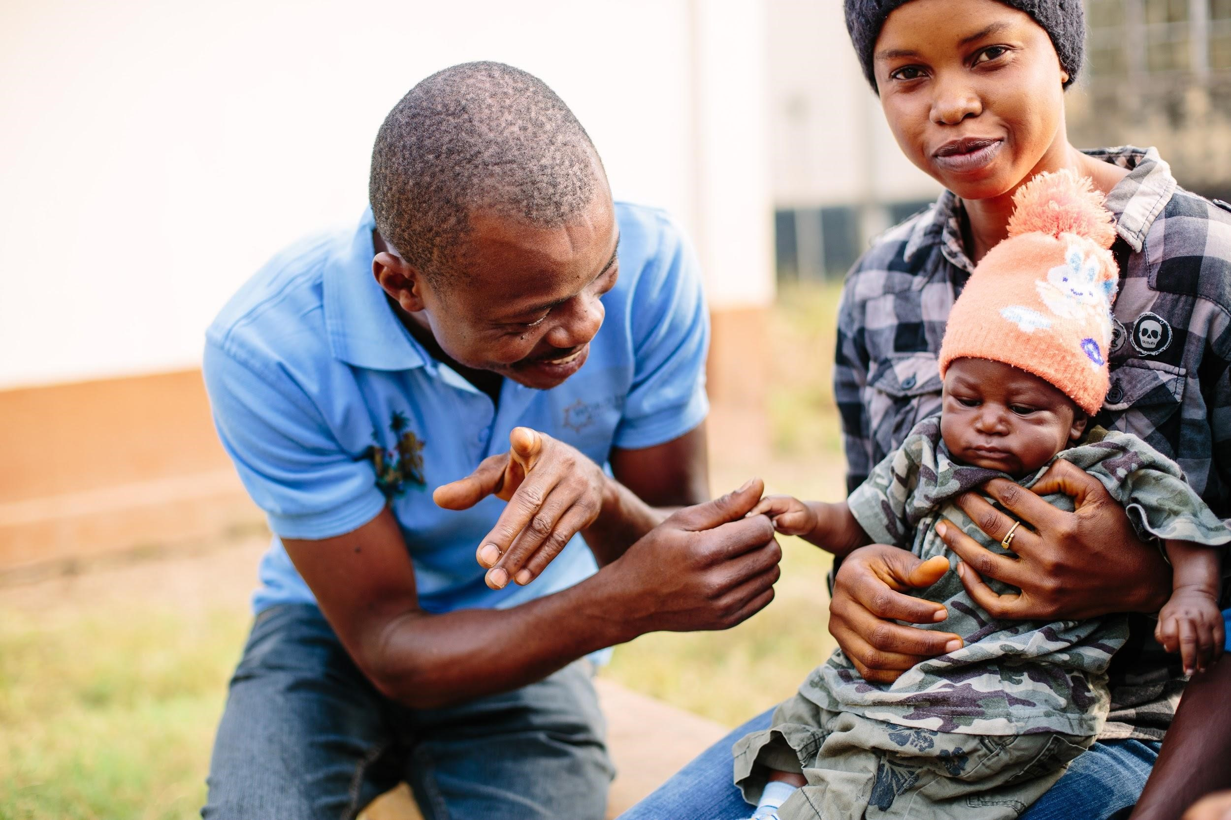 A male health worker smiles at an infant being held by his mother.