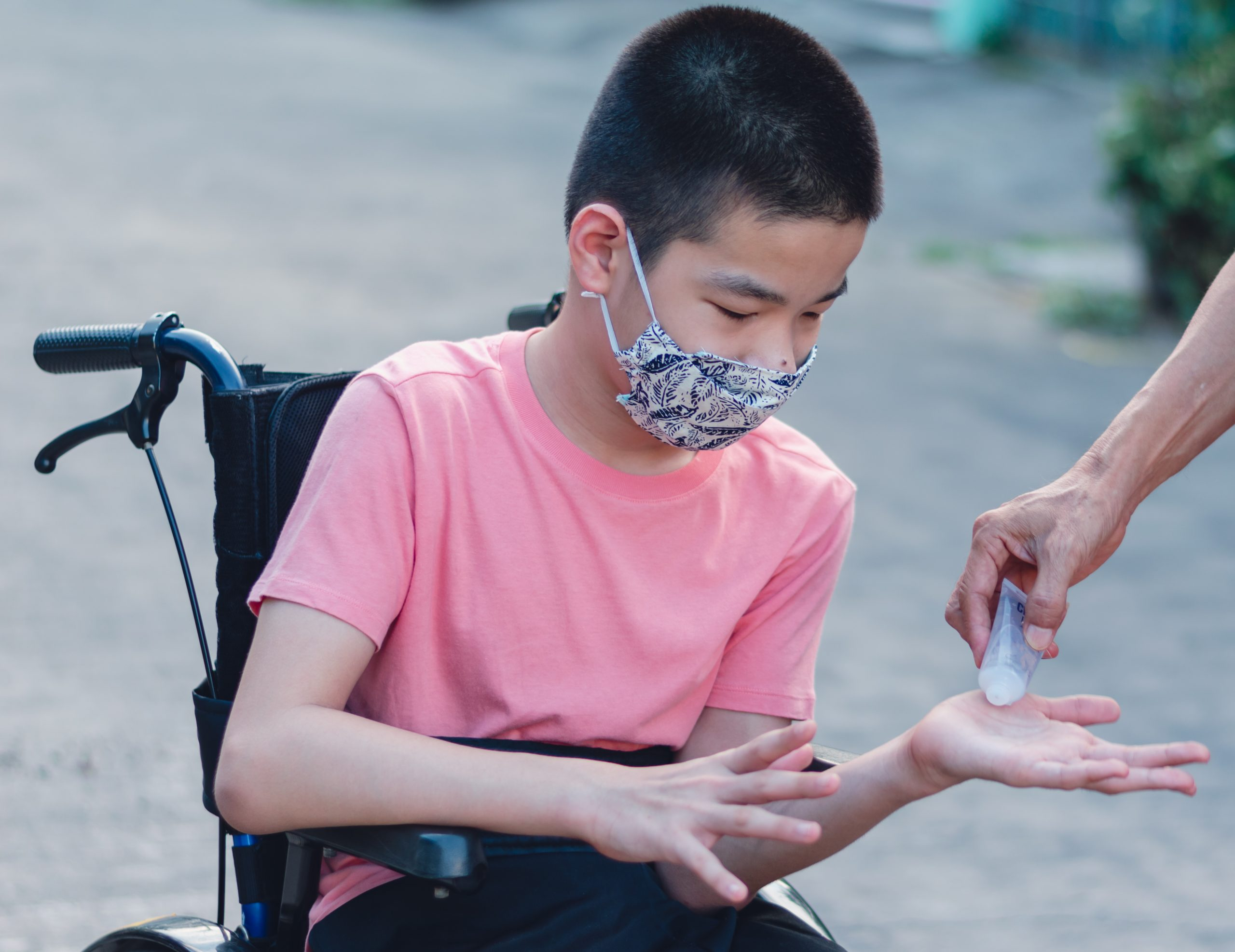 A young boy in a wheel chair receives hand sanitizer