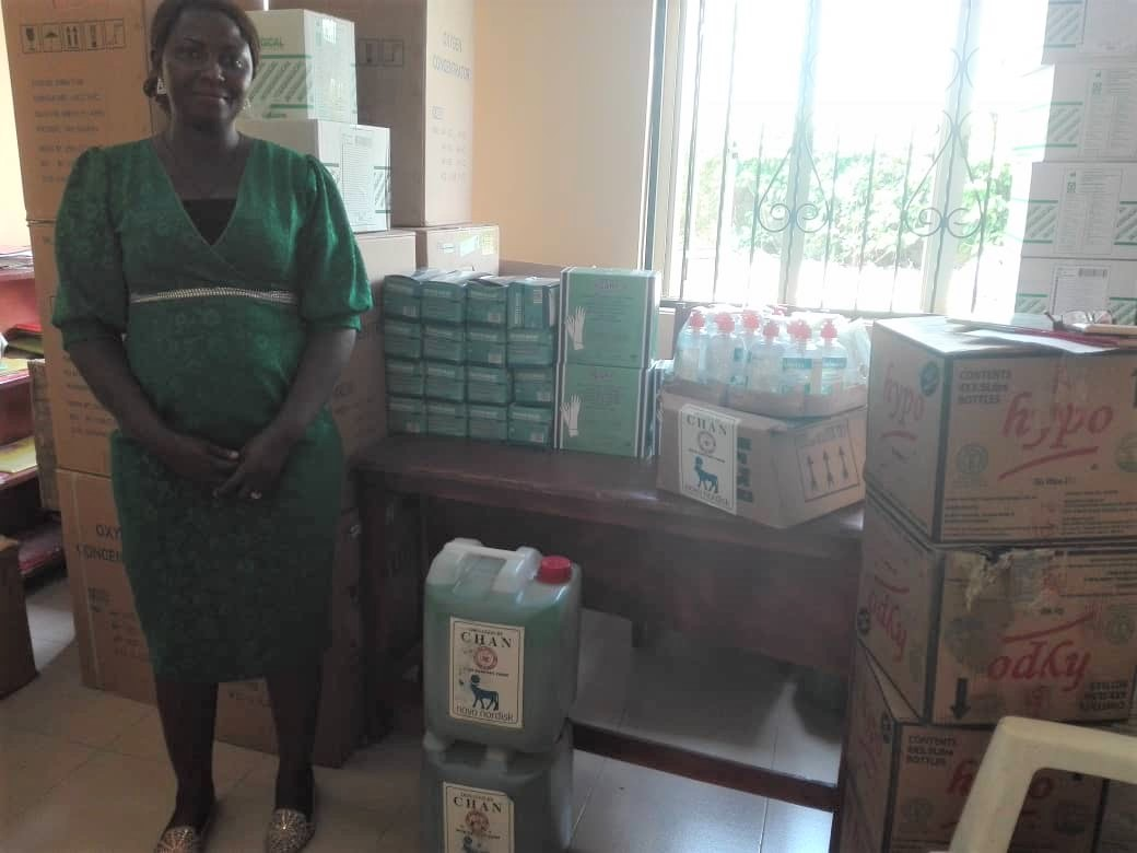 A woman stands next to supplies to mitigate COVID19