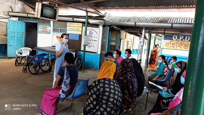 A nurse wearing a PPE mask talks to a group of people in India about COVID.