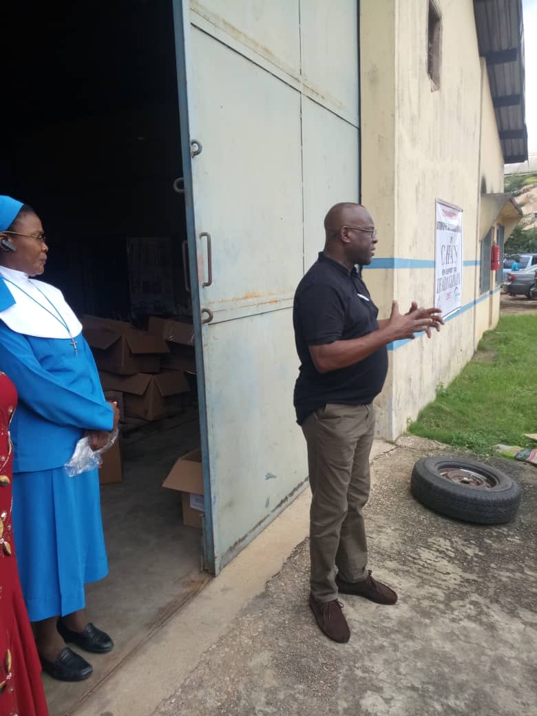 Mr. Mike Idah General Secretary of CHAN stands outside the office talking to people about personal protective equipment