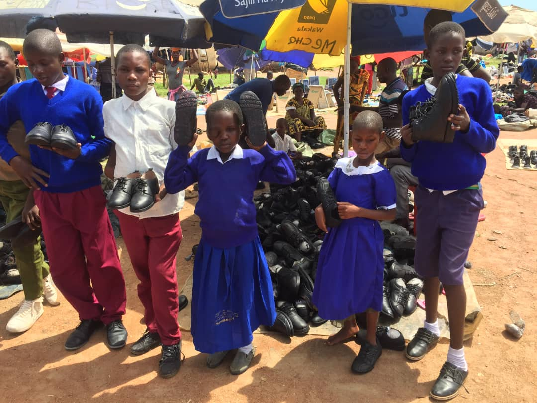 Children standing outside in Tanzania in new school uniforms