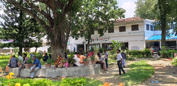 People sit around a tree in front of a health clinic in Bangladesh.