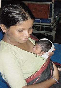 A mother holds a child on her chest in what is referred to as Kangaroo care.