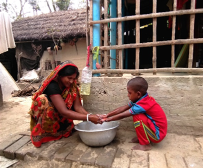 A mother and young child outside washing their hands with a large bowl.