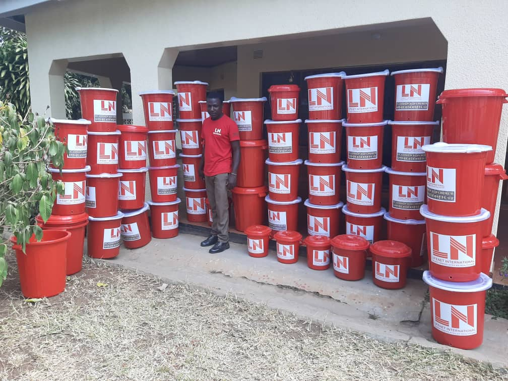 A man stands next to many containers of handwashing solution.