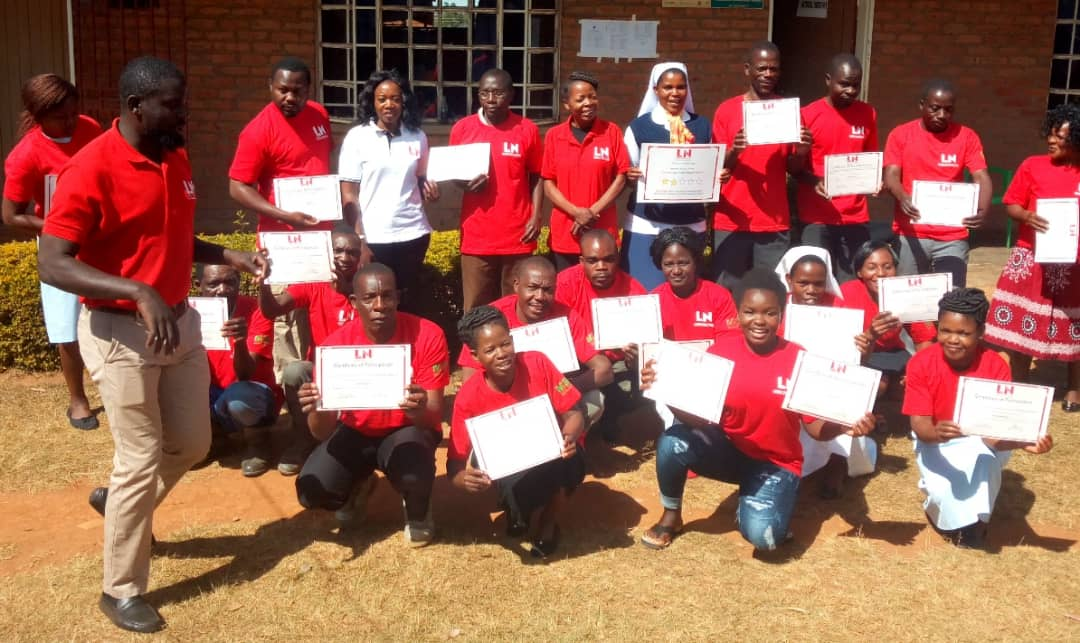 A group of people in matching red shirts display their health training certificates.