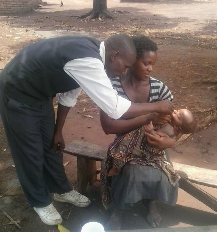 A man gives a child vitamin A orally while he lays on the lap of his mother in Malawi.