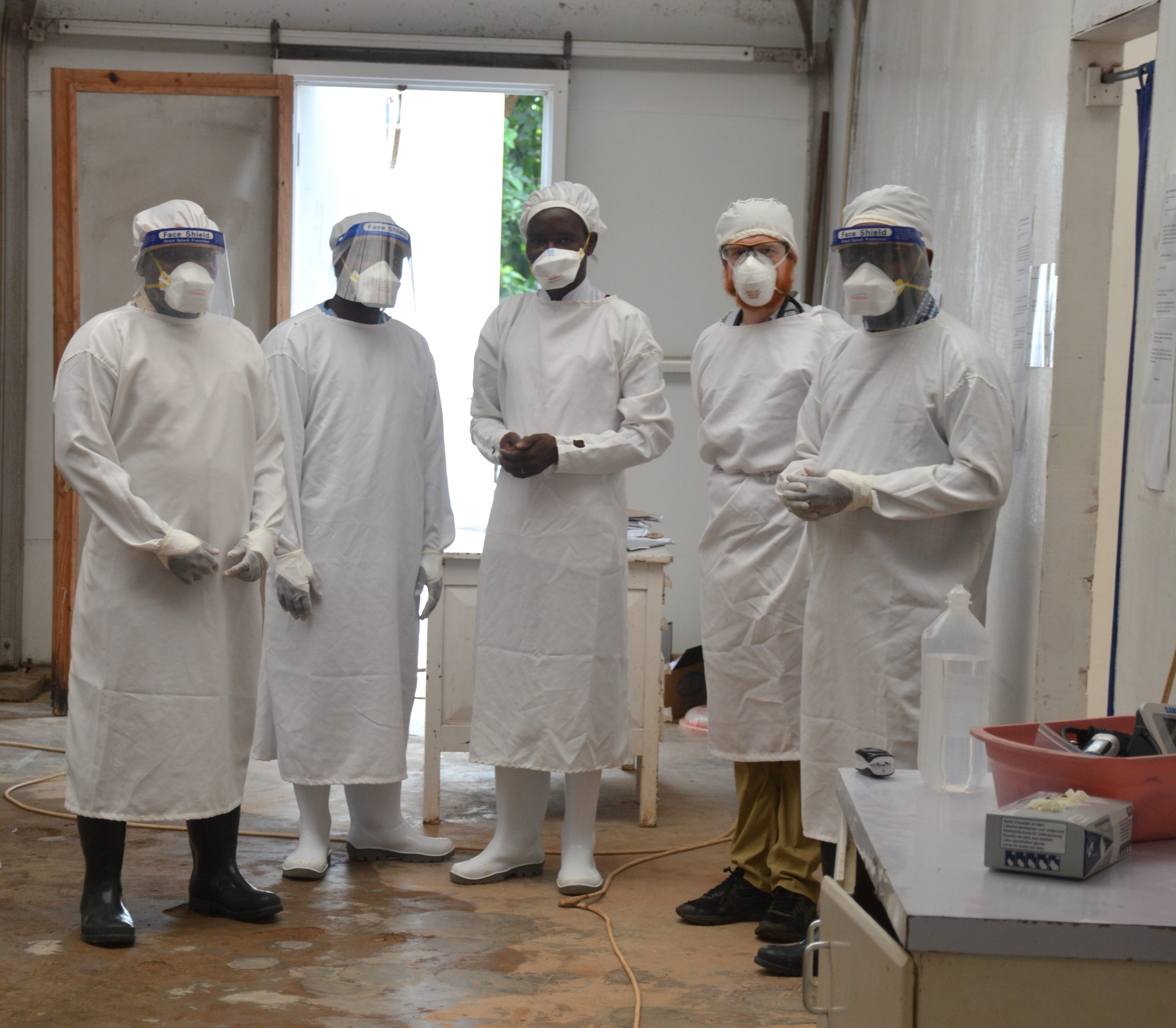 Five people in a health facility in full COVID personal protective great including masks and gloves.