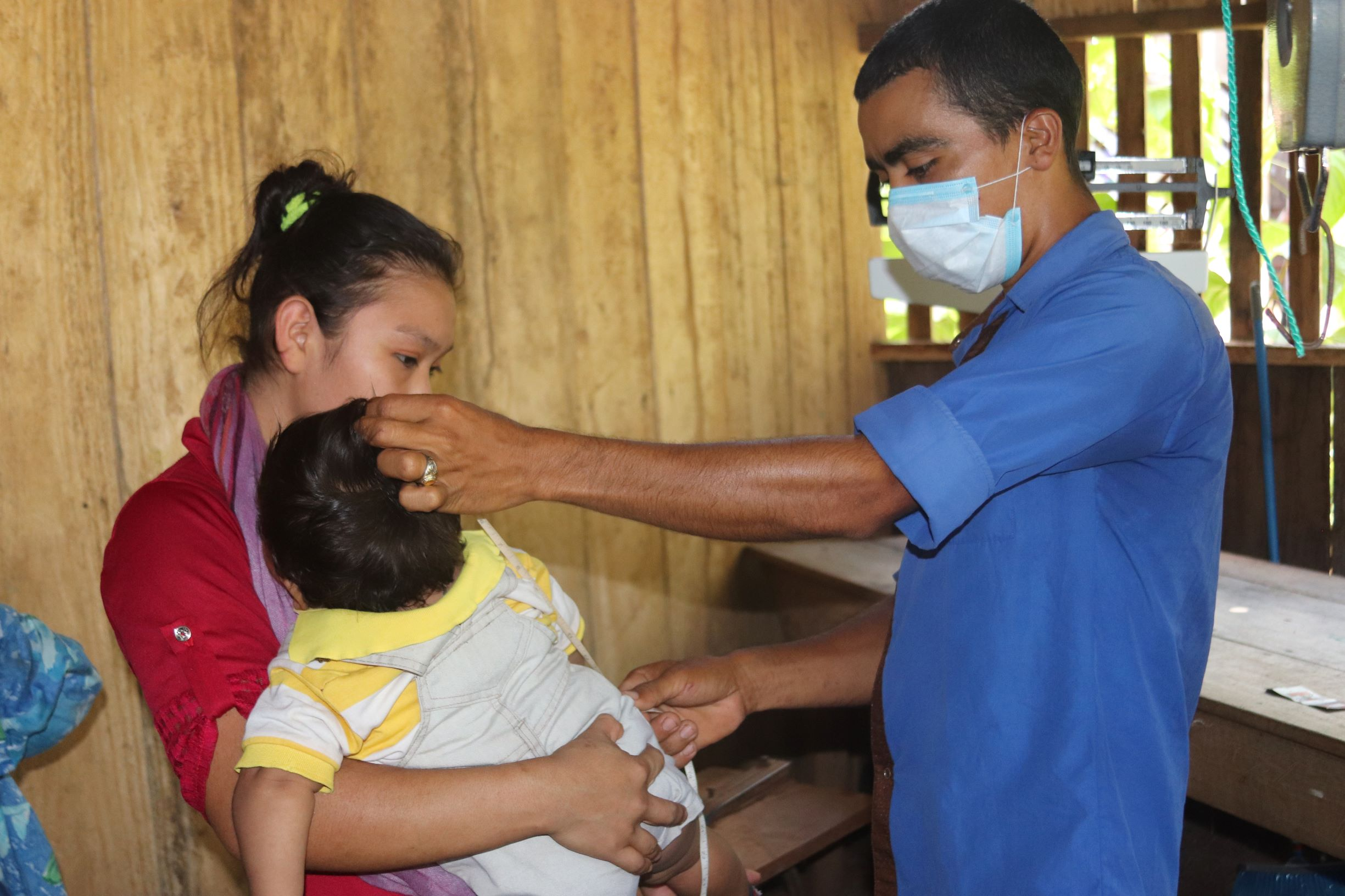 A community health worker measuring height of a baby.