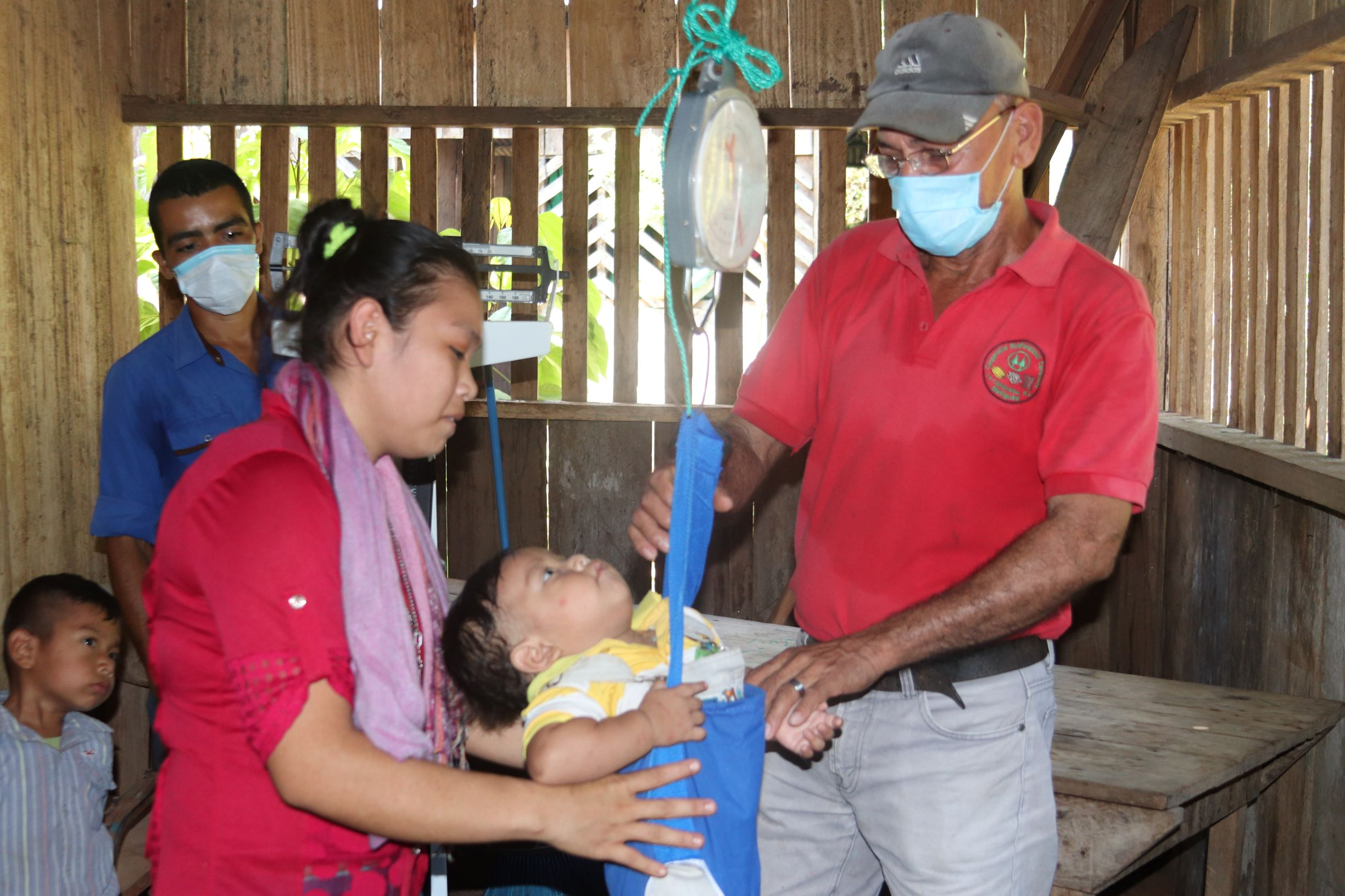 A health worker weighs a baby using a hanging scale.