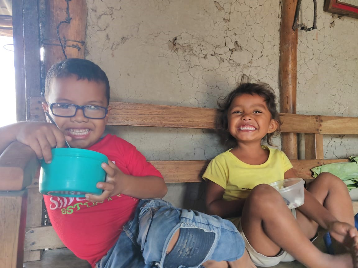 A young boy and girl eat in Nicaragua