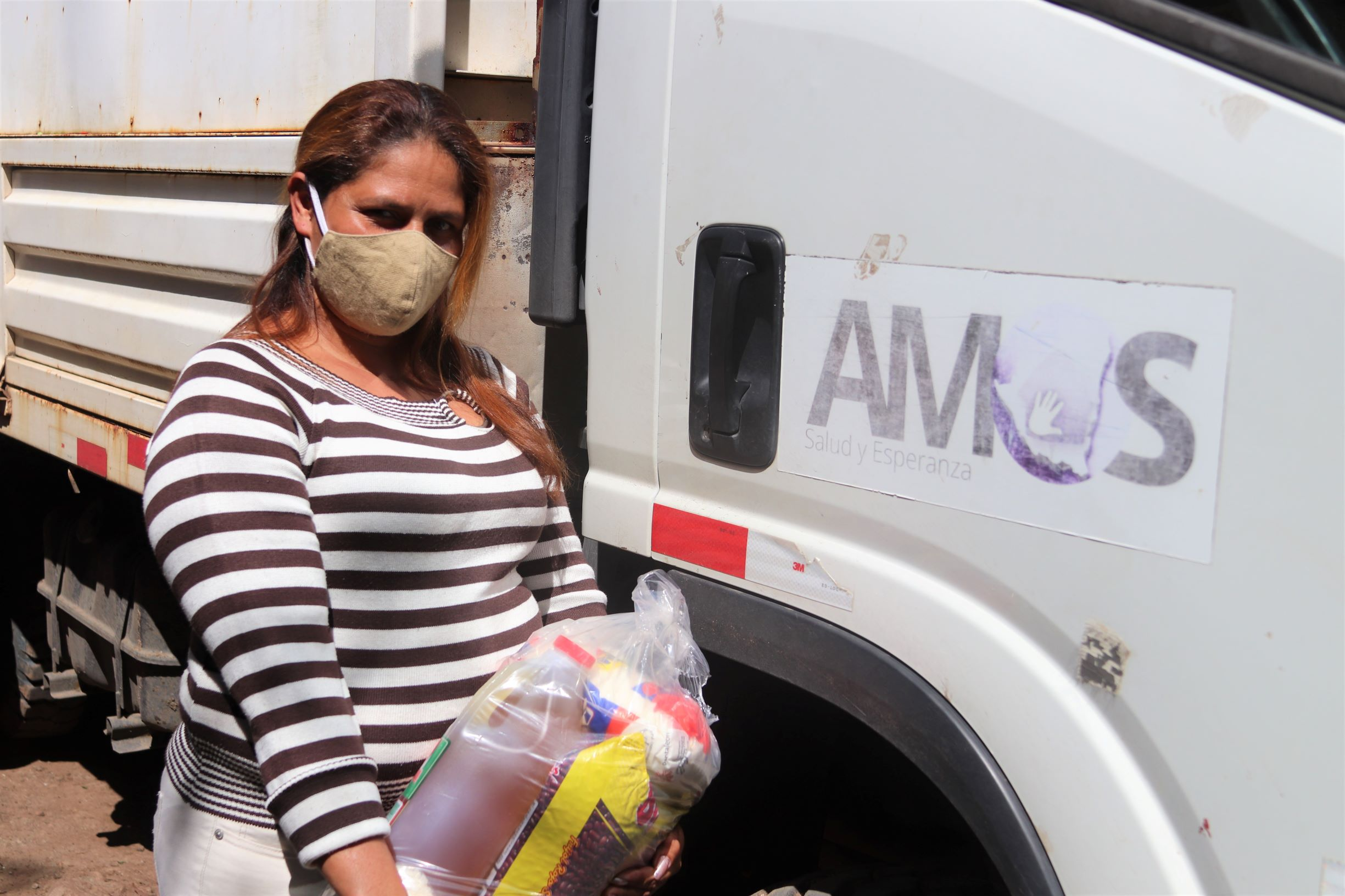A woman stands by a truck holding a bag of food.