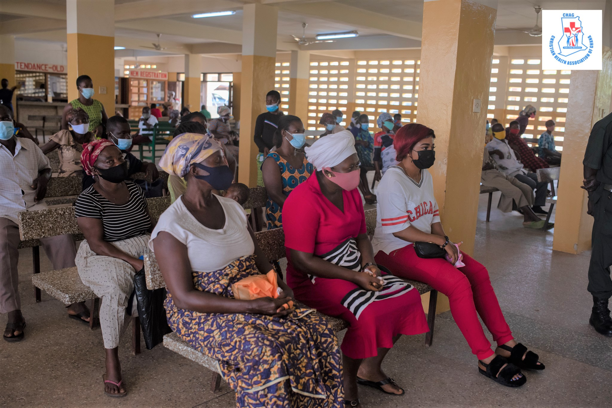 Women sit in rows listening to COVID educational messages