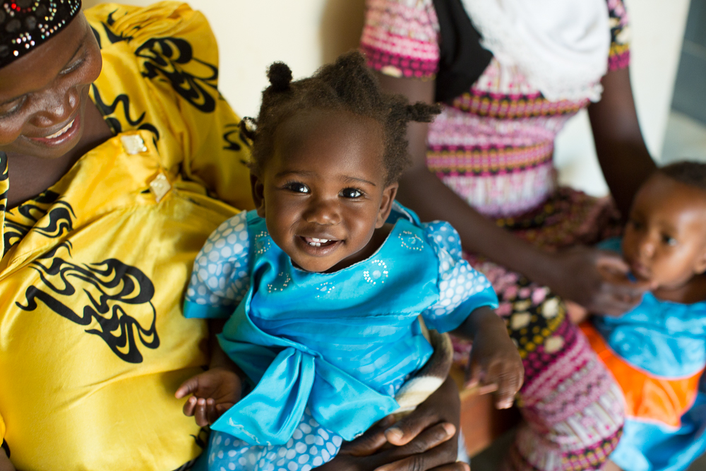 A young girl in Uganda in a blue dress sits on her mother's lap.