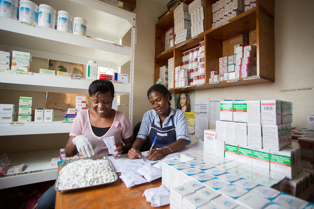 Two women sit at a table working in a pharmacy in a health facility in Uganda.