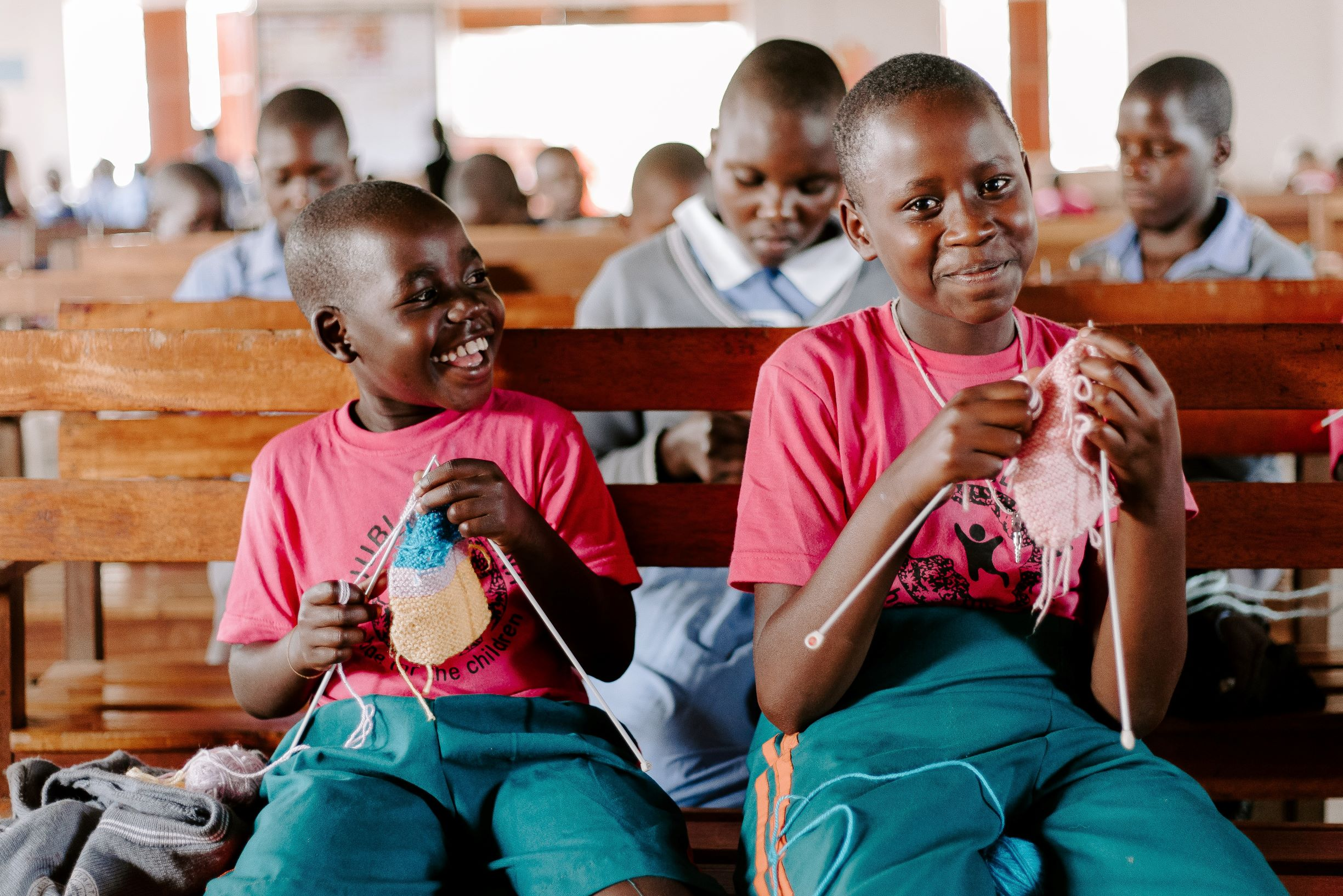Two boys in matching shirts and shorts knit in a church in Uganda.
